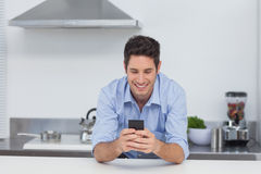 Man texting with his smartphone. Handsome man texting with his smartphone in kitchen Royalty Free Stock Image