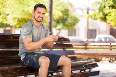 Man texting on his smartphone at a park. Portrait of a good looking Hispanic young man using a smartphone and texting before exercising and going for a run at a Stock Photo