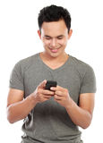 Man texting message. Young asian man texting message at his mobile phone isolated over white background Royalty Free Stock Photography