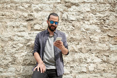 Man texting message on smartphone at stone wall. Leisure, technology, communication and people concept - smiling man texting message on smartphone at stone wall royalty free stock photos