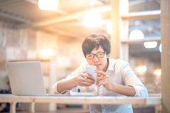 Man texting message on smartphone in workspace. Young Asian business man texting message on social media application by phone, casual professional entrepreneur Stock Image