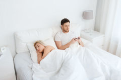 Man texting message while woman is sleeping in bed Royalty Free Stock Image