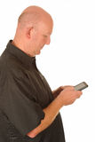 Man texting with mobile. Side portrait of middle aged bald man texting with mobile telephone, white background Royalty Free Stock Images