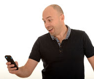 Man texting with mobile. Side portrait of middle aged bald man texting with mobile telephone, white background Stock Photo