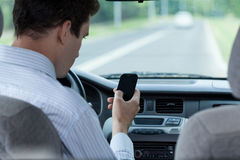 Man texting on mobile phone during driving a car Stock Photography