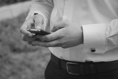 Man texting on mobile phone. Man in shirt with cufflinks texting on mobile phone at outdoor. Shallow depth of field Royalty Free Stock Photo