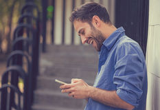 Man texting on mobile phone outdoors. Man texting on phone. Casual urban professional entrepreneur using smartphone smiling happy outside office building Stock Photography