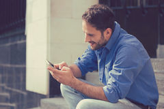 Man texting on mobile phone outdoors. Man texting on phone. Casual urban professional entrepreneur using smartphone smiling happy outside office building Stock Image