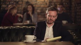 Man texting on notebook and drinking coffee in cafe stock footage