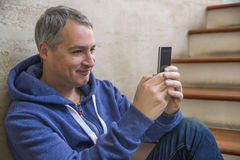 Man texting on phone. Casual urban professional entrepreneur using smartphone smiling happy. Inside office building. Indoor portrait of modern mature man with Royalty Free Stock Images