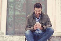 Man texting on phone. Casual urban guy using smartphone smiling happy outside old town building. stock photos