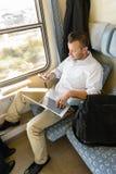 Man texting on phone holding laptop train Stock Image