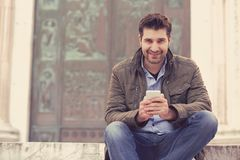 Man texting on a phone smiling at camera. Man texting on a phone. Casual urban professional entrepreneur using smartphone smiling happy at camera on background stock photo