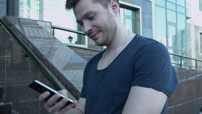 Man texting on phone. A young man with a smartphone writes sms near the building. A handsome young man in a T-shirt with stock footage