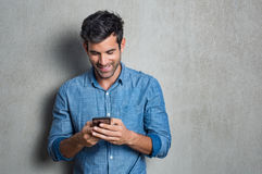 Man texting on phone. Young man texting message on smart phone isolated on grey background. Smiling latin man holding smartphone and looking at it. Happy stock photo