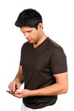 Man Texting On Smartphone. Young man sends a message by texting on his smartphone Stock Photos