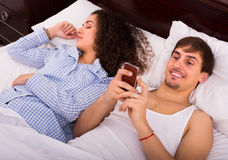 Man texting to lover as wife sleeping Stock Photography