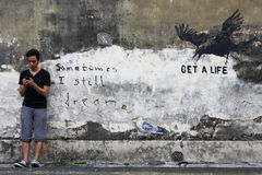 Man Texts. A man texts on his mobile phone while standing against a wall. On the wall is a street art where a seagull is being bullied by a crow for being Stock Photo