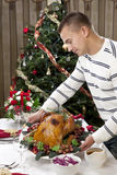 Man Thanksgiving christmas roasted turkey. Man with Garnished Thanksgiving roasted turkey to celebrate traditional family dinner with salad, fruits, vegetables stock photography