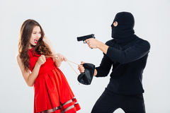Man theif threatening with gun and stealing young woman bag Stock Image