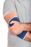 Man with a therapeutic elastic band on his elbow Stock Photography