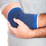 Man with a therapeutic elastic band on his elbow Royalty Free Stock Photography