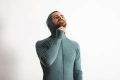 Man in thermal baselayer wear ninja suit set. Attractive young bearded athlete lock zip while wearing hood of his wither snowboard baselayer thermal suite Stock Images
