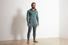 Man in thermal baselayer wear ninja suit set. Young athlete wers green merino wool baselayer thermal suite in winter time, posing in front of white wall Royalty Free Stock Photos