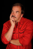 Man thinking. A studio portrait of a man in red cowboy shirt, crossing arms while thinking.  Model looks somewhat like Burt Reynolds.  Black background Royalty Free Stock Photos