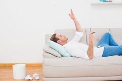 Man thinking on couch with writer block. At home in the living room Royalty Free Stock Photo