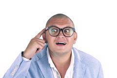 Man thinking while doing a silly face with nerd glasses Royalty Free Stock Photo