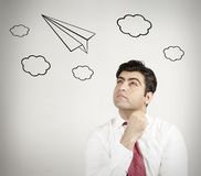 Man thinking of flying on a paper plane Royalty Free Stock Photos