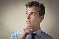 Man thinking with his hand on his chin. Young male wondering about something Stock Photography