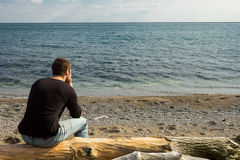 Man thinking on a log. A man sitting on a log looking out to the sea and thinking Royalty Free Stock Photography