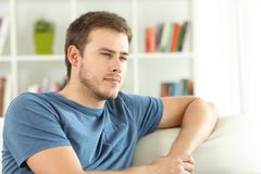 Man thinking looking away at home. Serious man thinking looking away sitting on a couch in the living room at home Stock Images
