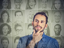 Man thinking looking up at group of multicultural happy people. Portrait of a handsome young men thinking looking up at a group of multicultural happy people Stock Photos