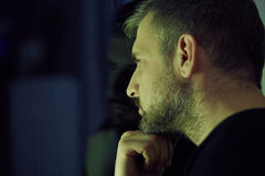 Man thinking and looking through the window Stock Images