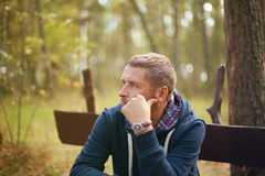 Man thinking moody portrait, sitting at autumn park Stock Photography