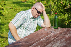 Man thinking near bottle of alcohol on table Royalty Free Stock Photos