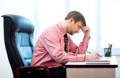 Man thinking in the office. Young businessman is sitting in chair at his cabinet Stock Image