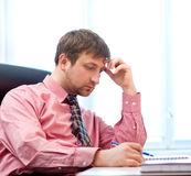 Man thinking in the office. Young businessman is sitting in chair at his cabinet Royalty Free Stock Photos
