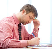 Man thinking in the office. Young businessman is sitting in chair at his cabinet Royalty Free Stock Images