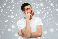 Man thinking over snow on gray background Royalty Free Stock Images