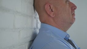 Man Thinking Pensive Near a Brick Wall Inside Office Room royalty free stock images