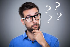 Man thinking with question marks stock image