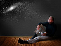 Man thinking. A man reclines on a wooden floor with an open journal thinking and dreaming about the universe stock photography