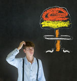 Man thinking scratching head chalk nuclear bomb cloud blackboard background Royalty Free Stock Photography