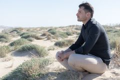Man thinking. Sitting on the sand of the beach, with light pants and black shirt and beard of a few days Stock Images