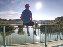Man thinking. Sportsman in blue t-shirt and black pants sit on pier royalty free stock photo
