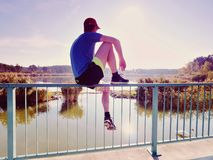 Man thinking. Sportsman in blue t-shirt and black pants sit on pier royalty free stock photography